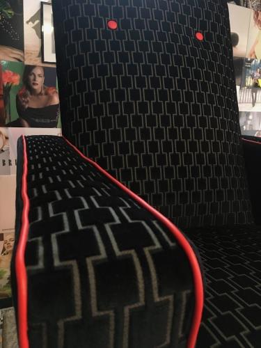 Detail armsteunen vintage zetel met geometrische stof en rode bieskoord in kunstleder