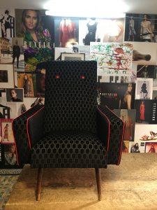 Vintage zetel geherstoffeerd in geometrische stof met rode accenten in de bieskoord en de knopen
