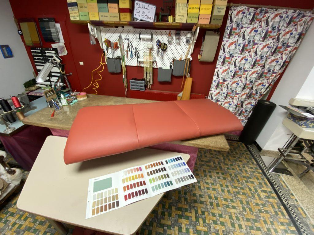 Lederen zitkussen op werktafel met stalenkaart van de beschikbare kleuren