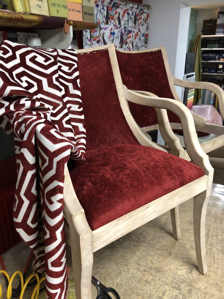 Twee stoelen op de werktafel, nieuw geherstoffeerd met een stuk rode stof op de stoelen gedrapeerd.