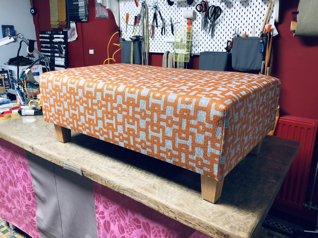 Voetbank geherstoffeerd in een geometrische print. De overheersende kleuren zijn oranje en grijs. De voetbank staat op een verhoogde werktafel