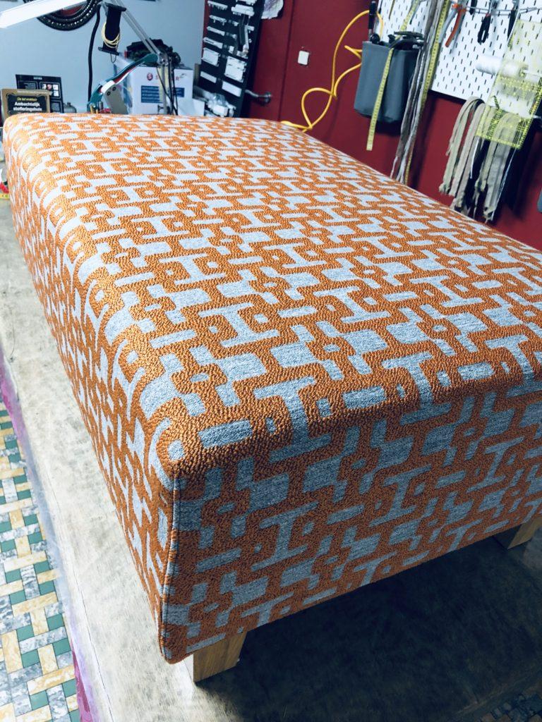 Bovenaanzicht van een voetbank in geometrische stof bekleed met oranje en grijze kleuren. De voetbank staat op een verhoogde werktafel