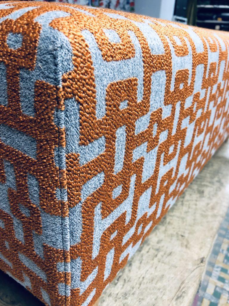 Detailfoto van de hoek van een voetbank. Het sierstiksel is zichtbaar. De voerbank is bekleed in grijs, oranje stof met geometrische print