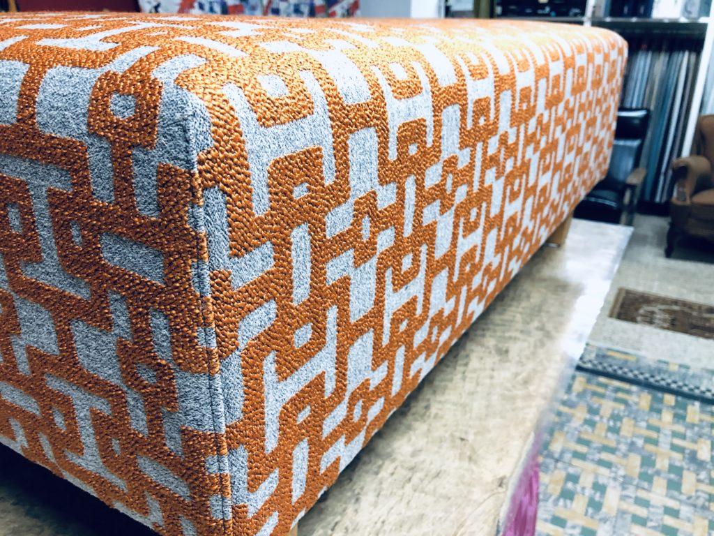 Close-up foto van een voetbank opnieuw geherstoffeerd in geometrische print. De kleuren zijn oranje en grijs. De voetbank staat op een verhoogde tafel