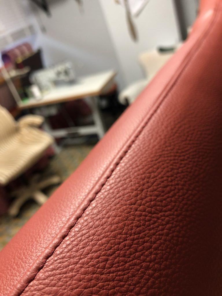Close-up van het sierstiksel van een rood lederen kussen