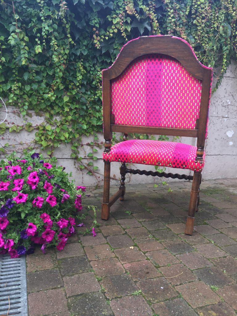 Achterkant geherstoffeerde antieke stoel in felroze kleuren