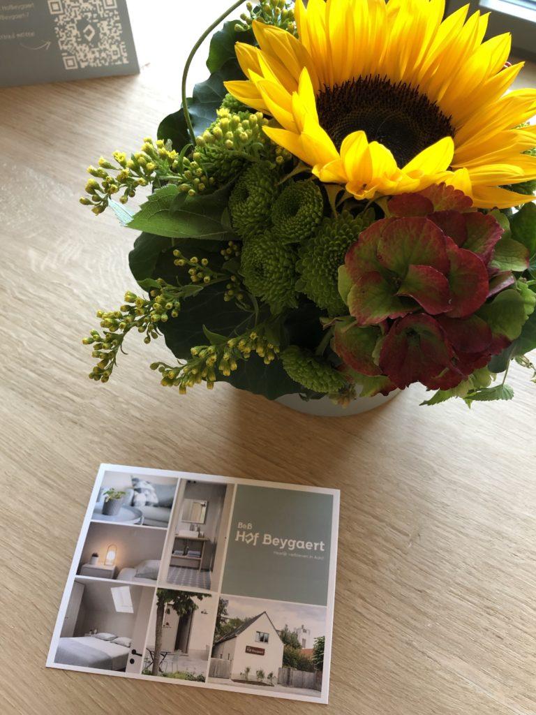 Boeketje met zonnebloem op tafel met flyer 't Hof Beygaert