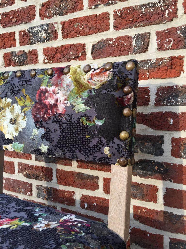 Detailfoto grote siernagels van stoel bekleed in rijkelijke stof met bloemenprint