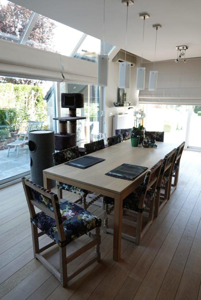 Eetkamer met grote tafel en stoelen opnieuw bekleed in rijkelijke stof