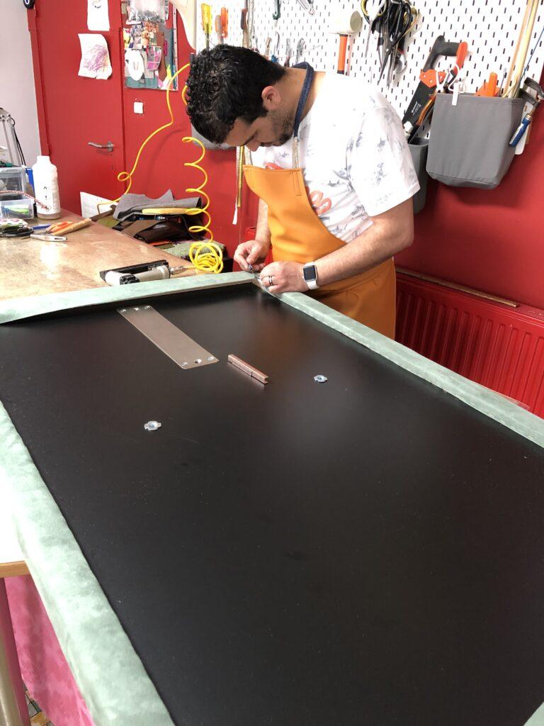 stof wordt strak aangespannen en vastgehecht aan het frame
