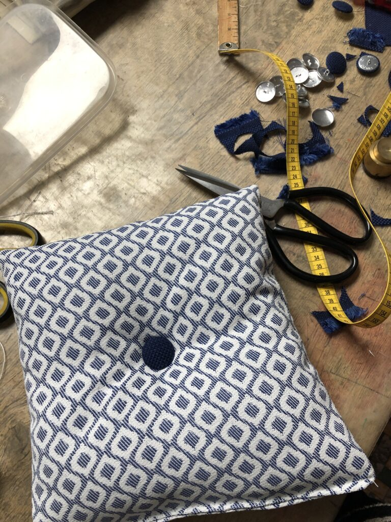 klein sierkussen met blauwe knop op werktafel
